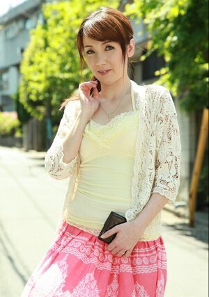 Far eastern beauty with red hair seductively walks on sunny street of big city