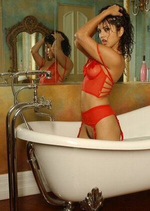 Adult video star from India gets in the bathtub and besides takes her red top off showing jugs