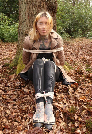 Broad with glasses can't stand up because she is hogtied by the tree